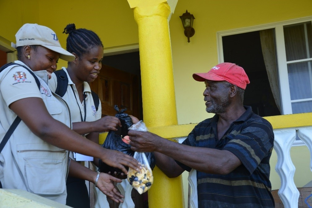 Household beneficiary Thomas Davis shows his appreciation to ZAP Vector Control Technicians by giving them local fruits, such as ackee, coconuts, and plantains from his land. Photo: Laura McCarty/Abt Associates